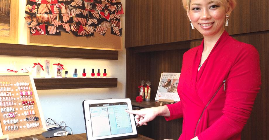 iPadレジの「ユビレジ」を指差す山崎店長