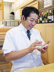 スマートフォンを操作する三浦友久専務