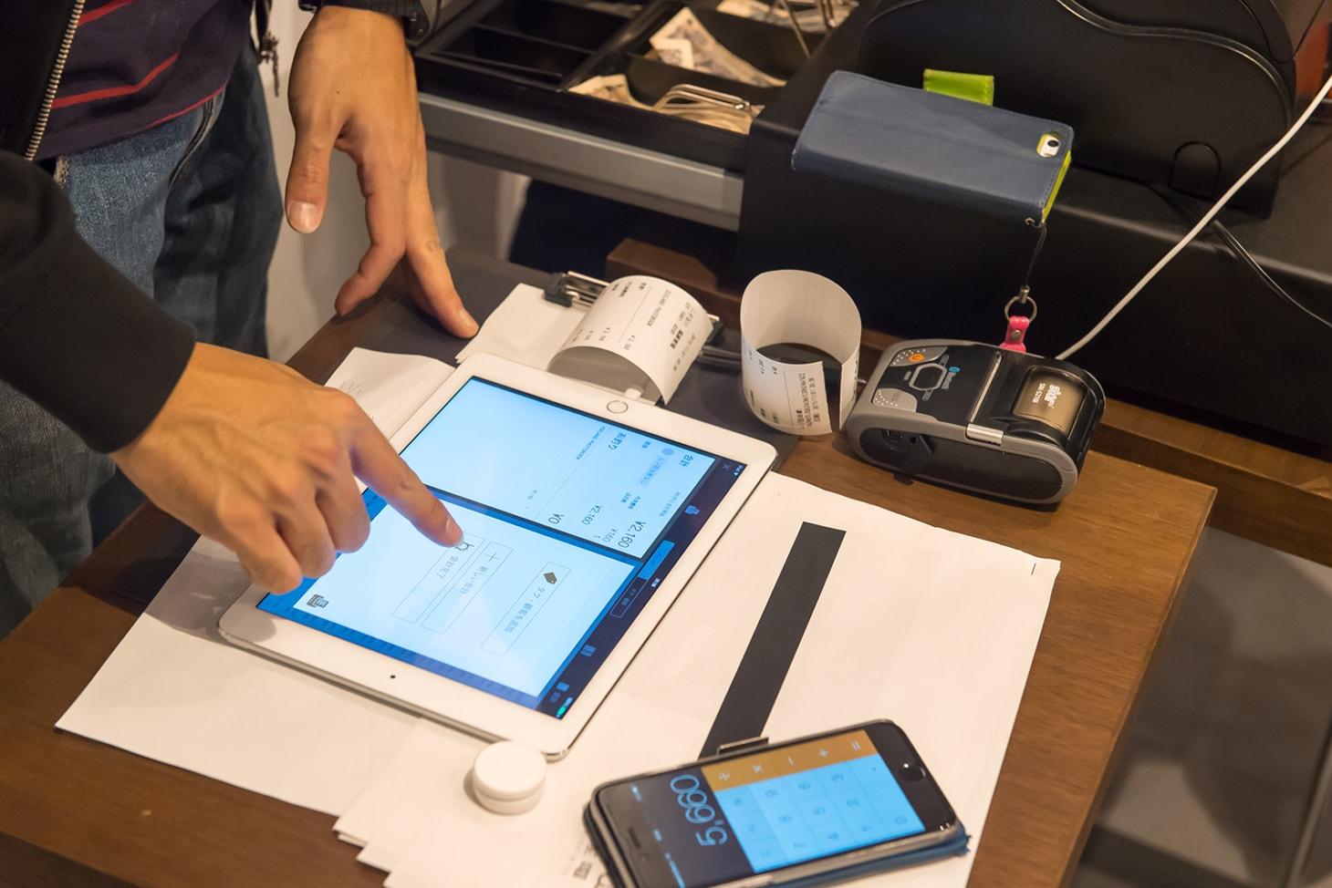 iPadでユビレジを操作するスタッフの写真